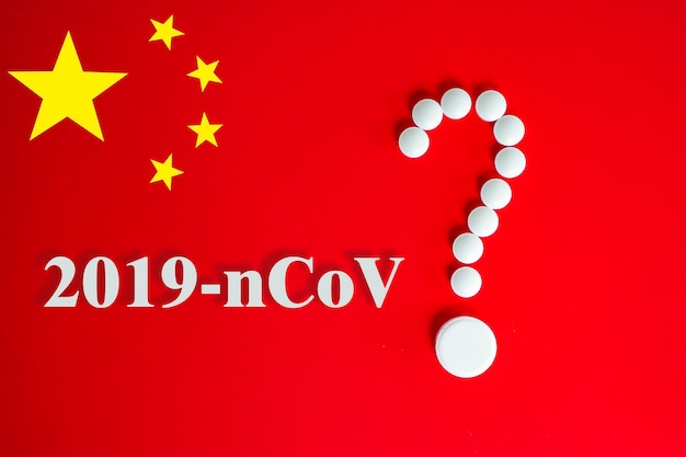 White pills in the form of a question mark on a red background with inscription 2019-ncov and copy space for text. red background of the chinese flag. 2019 novel coronavirus 2019-ncov concept.