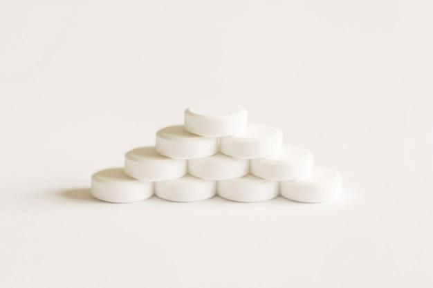 Белые таблетки, формирующие пирамиду на белом фоне