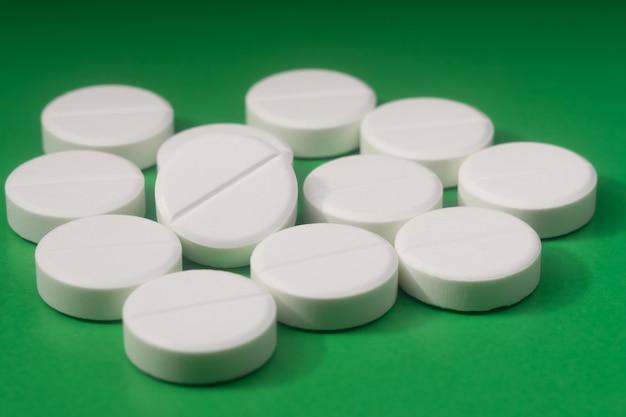 White pills on greenbackground