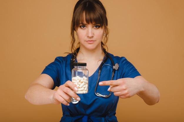 Белые таблетки в банке женщина-врач. врач показывает витаминные капсулы. лекарственные капсулы.