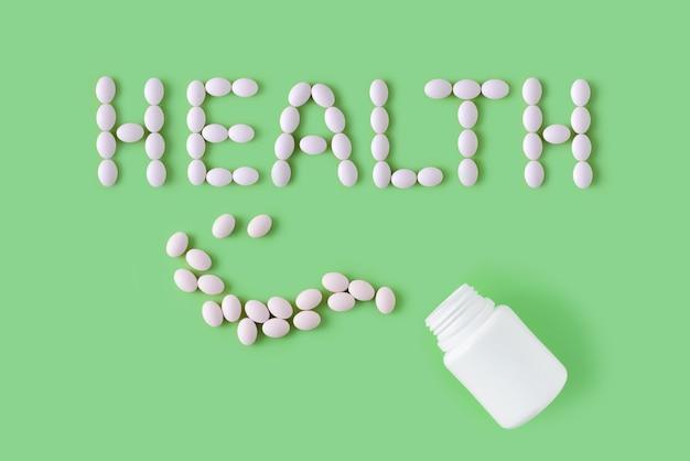 単語の健康と緑の背景の上にボトルの形で白い錠剤。