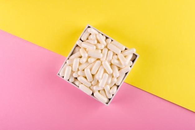 パステルカラーの背景に分離された白い錠剤。薬と処方薬のフラットは背景を築きました。