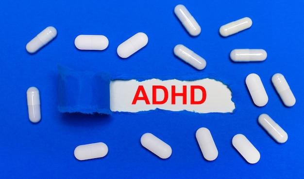 흰색 알 약은 아름 다운 파란색 배경에 거짓말. 중앙에는 adhd라는 비문이있는 백서가 있습니다. 의료 개념. 위에서 봅니다.