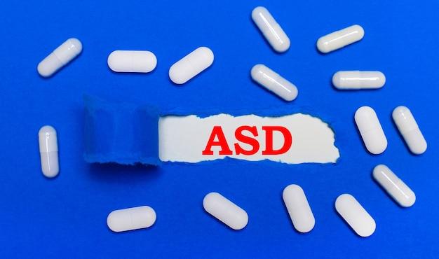 白い錠剤は美しい青い背景の上にあります。中央には、asd自閉症スペクトラム障害の碑文が書かれたホワイトペーパーがあります。医療の概念。上からの眺め。