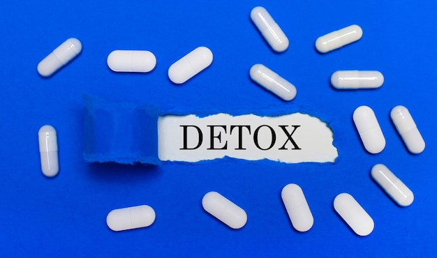 白い錠剤は美しい青い背景の上にあります。中央にはデトックスと書かれたホワイトペーパーがあります。医療の概念。上からの眺め。