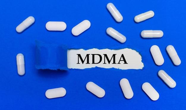 Белые таблетки лежат на красивом синем фоне. в центре - белая бумага с надписью mdma. медицинская концепция. вид сверху.