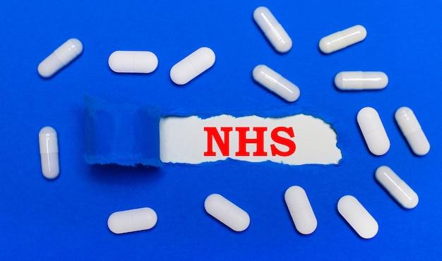 Белые таблетки лежат на красивом синем фоне. в центре белый лист с надписью nhs. медицинская концепция. вид сверху.