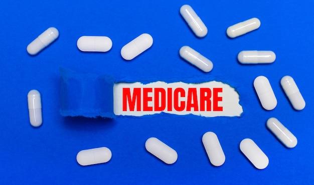 흰색 알약은 아름다운 파란색 표면에 놓여 있습니다. 중앙에는 medicare라는 문구가있는 백서가 있습니다. 의료 개념. 위에서 봅니다.