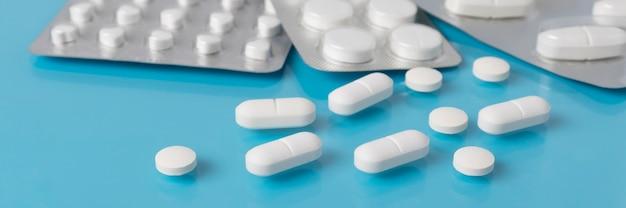 青い医者のテーブルの上の白い錠剤。薬局、医学、薬理学、医薬品生産の概念。