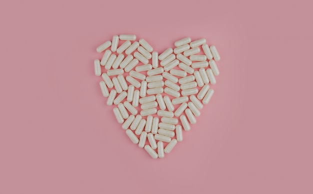 White pills on a pink wall. scattered tablets. heart made of pills.