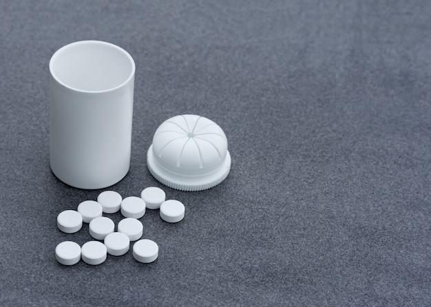 白い錠剤は灰色の背景と開いているボトルに散在しています。上面図のクローズアップ。あなたのテキストのためのスペースを