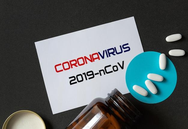 흰색 알 약 toppled 갈색 병 및 백서 비문에서 흘리 고. 코로나 바이러스 치료 개념.