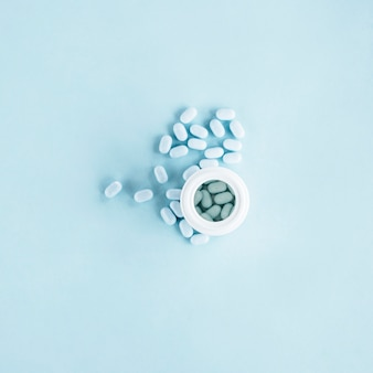 White pills with open plastic bottle on blue background