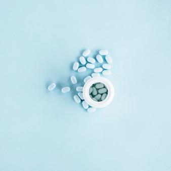 青い背景に開いたプラスチックボトルと白い丸薬