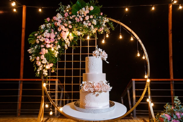 Бело-розовый красивый свадебный торт на фоне вечерней свадебной арки.