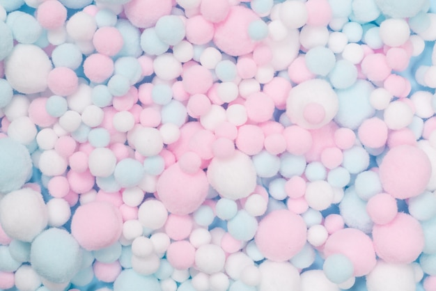 White, pink and blue soft pompons as a background. bright background.