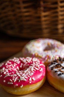 White, pink and brown glazed donuts on wood