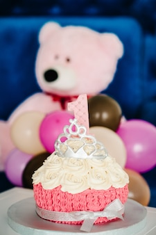 White and pink cake with candle 1 year and crown on top of it. one year birthday decorations. decorations for holiday party with balloons colors.