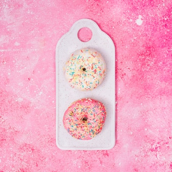 White and pink donuts with colorful sprinkles on tray over the pink textured background