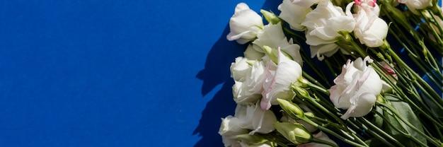 Белый розовые цветы эустомы на синей поверхности в винтажном стиле. вид сверху. белый цветок лизиантуса. формат баннера для поздравления свадебные пригласительные билеты. копирование пространства