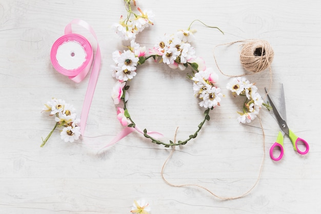 White and pink floral wreath with pink ribbon; spool and scissor on table