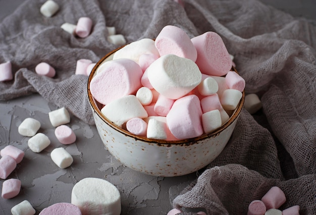 White and pink marshmallows on gray concrete background. selective focus
