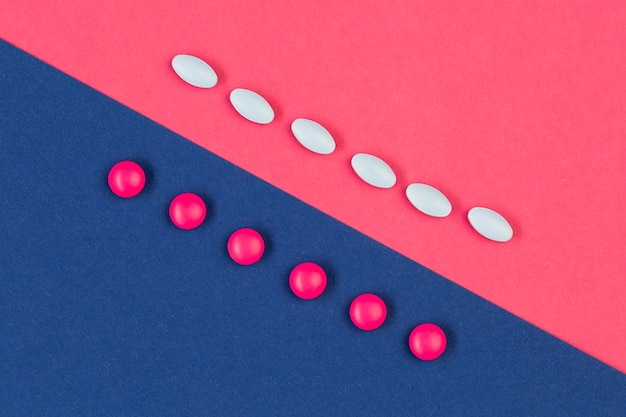 White and pink pills on desk