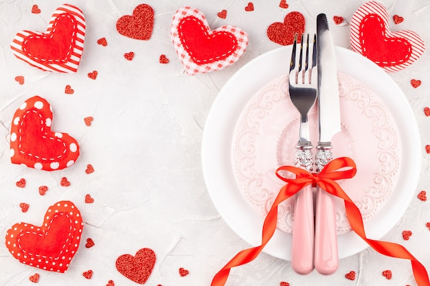 White and pink plates with fork, knife and red ribbon bow with decorative hearts