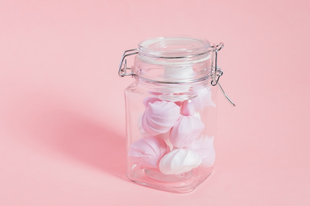 White and pink twisted meringues in a glass jar on pink background