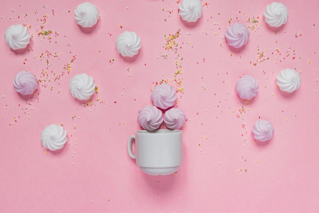 White and pink twisted meringues in porcelain bowl and colorful peakles on pink