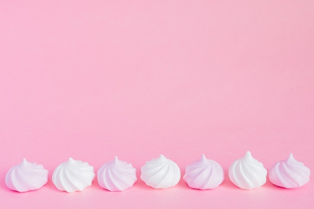 White and pink twisted meringues in a row on pink background, greeting card, copy space