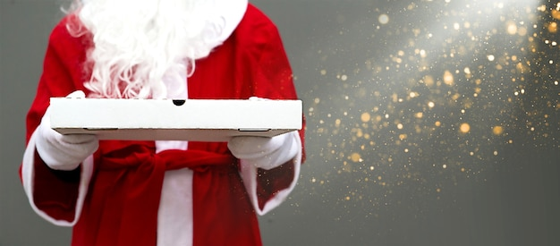 White pizza box in hands of santa claus in mittens, with a beard, in a red coat. christmas fast food delivery. new year's eve promotion. work on public holidays catering. copy space, mock up. banner