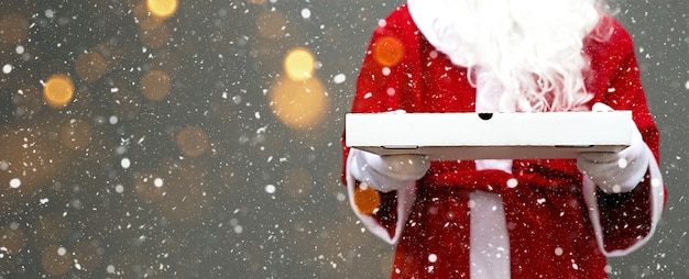 White pizza box in the hands of santa claus, with a beard, in a red coat. christmas fast food delivery. new year's eve promotion. work on public holidays catering. copy space, mock up. banner