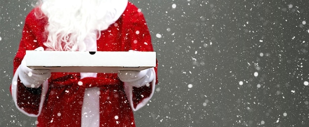 White pizza box in hands of santa claus with beard in red coat christmas fast food delivery new