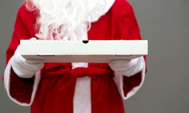白いミトンのサンタクロースの手に白いピザの箱