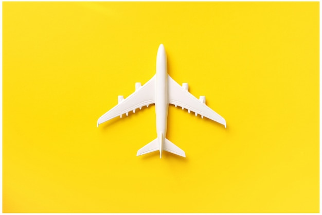 White plane, airplane on yellow color background with copy space.
