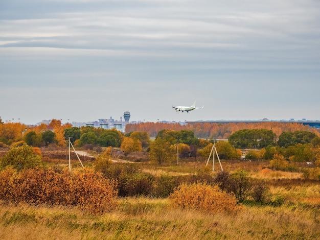白い飛行機が曇り空に着陸します。秋のサンクトペテルブルク。