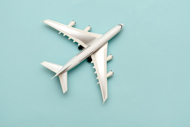 The white plane lies on a blue background. travel concept. creative idea of flying on an airplane.