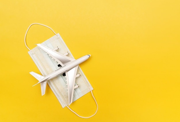 The white plane lies on a medical protective mask. travel concept. on a yellow background.