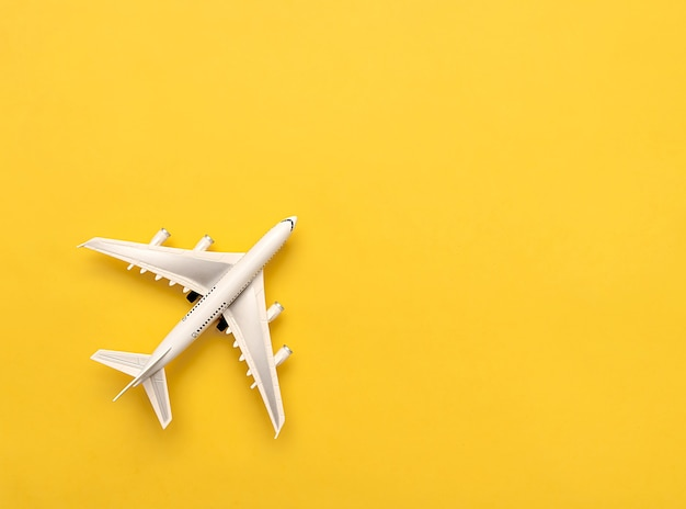 The white plane lies on a yellow background. travel concept. creative idea of flying on an airplane.