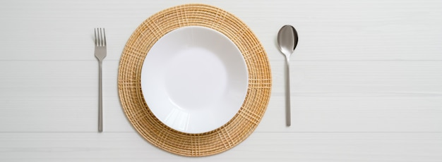 White plank dinning table with white ceramic plate on placemat and silverware