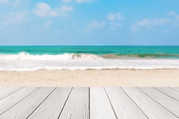 Стол белой доски деревянный перед крупным планом предпосылки пляжа песка моря или океана крайним. 3d рендеринг