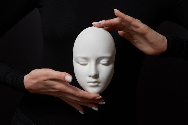 White plaster mask face is holding woman's fingers on a black wall, copy space. concept social psychological masks
