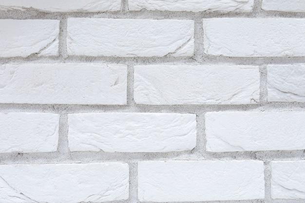 Белая отделка гипсокартоном с крупным планом образца кирпича.