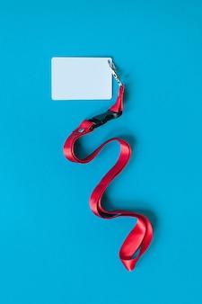 Белый пластиковый значок и красный шнурок с макетом пустого пространства, изолированные на синем фоне