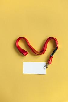 白いプラスチックのバッジ、赤いストラップ