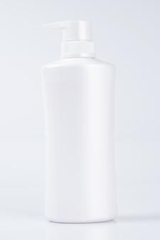白いプラスチック製のボトルコンテナーのモックアップ、白い壁に分離された製品テンプレートのパッケージ
