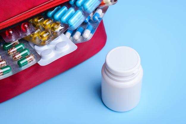 알약과 캡슐 흰색에 빨간 가방 근처 흰색 플라스틱 병