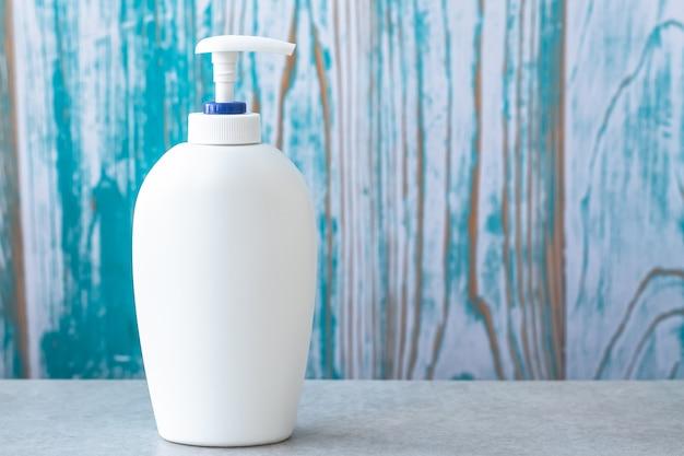로션의 흰색 플라스틱 병, 디스펜서와 비누. 욕실 세면 용품. 빈 곳. 위생 개념.