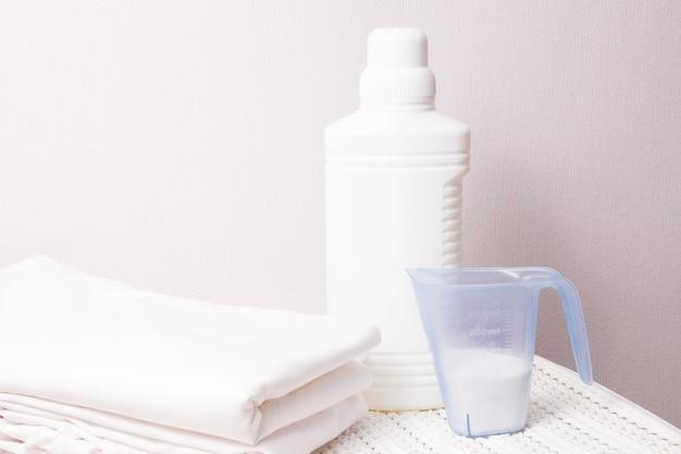 Белая пластиковая бутылка с отбеливателем и стиральным порошком в мерной чашке на белой пластиковой корзине